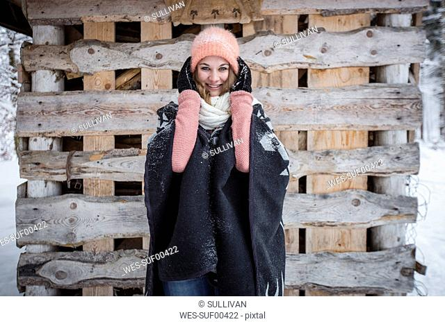 Portrait of smiling young woman in front of wood pile outdoors in winter