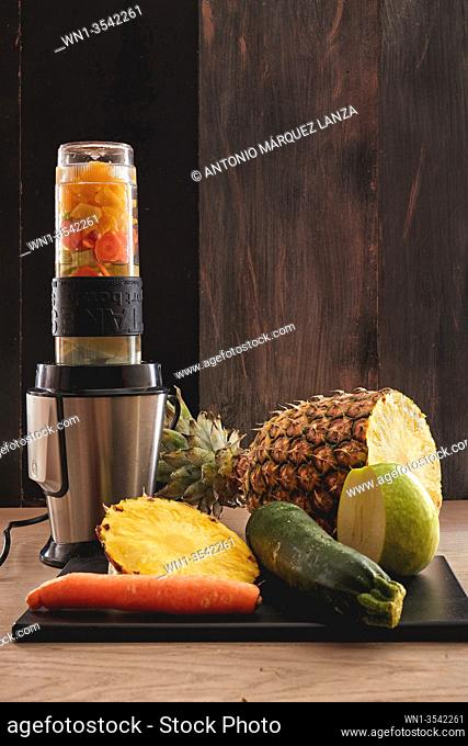 veggie juicy made in a blender of pineapple, apple, cucumber and carrot in a dark background