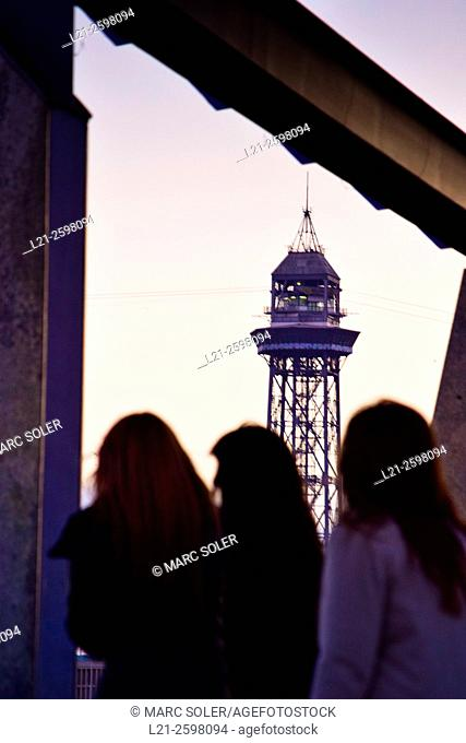 Cable car tower at dusk. Silhouette of three women back. Barcelona, Catalonia, Spain