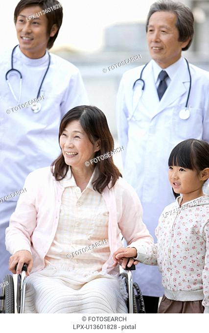 Hospital Staff with Mature Woman and Granddaughter