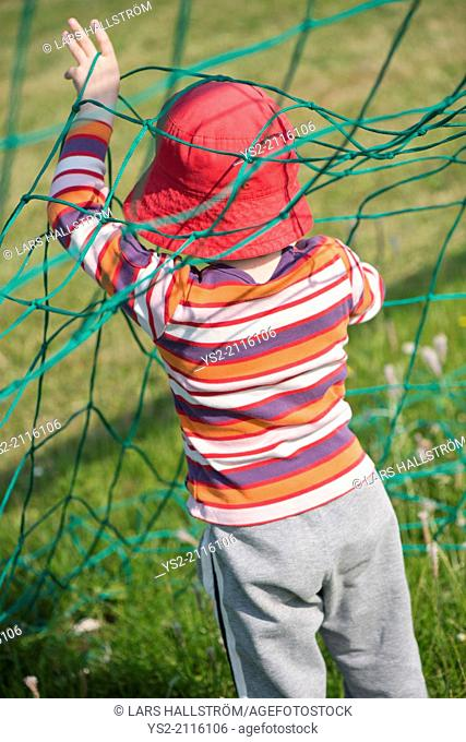 Young girl playing with net of football (soccer) goal