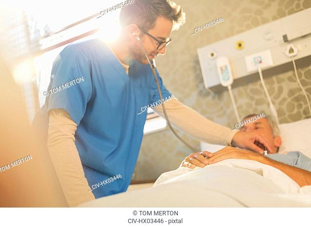 Male nurse using stethoscope on patient in hospital bed