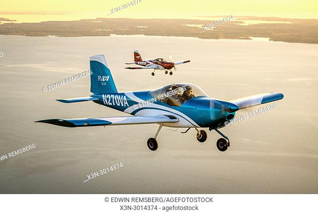 Two Vans RV-12 light sport aircrafts fly in formation together over the coastline of the Chesapeake Bay, Stevensville, Maryland, USA