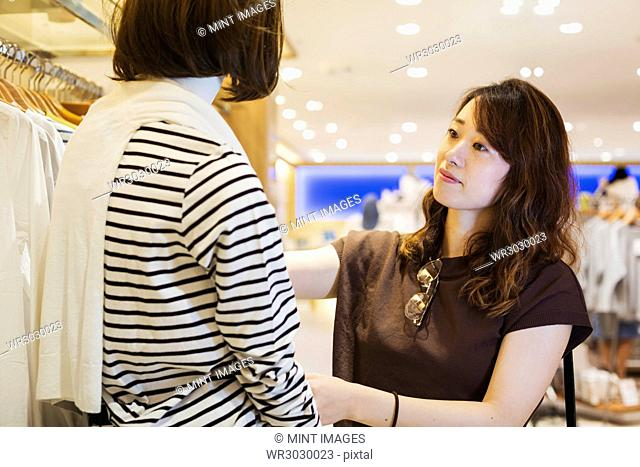 Woman with brown hair wearing brown shirt standing indoors, looking at clothing in a shop