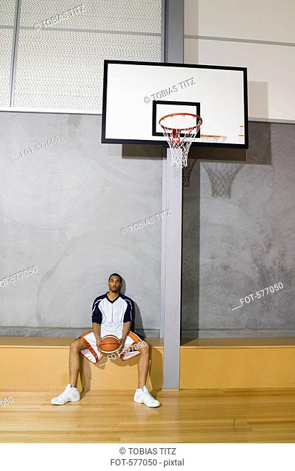 A young man sitting and holding a basketball between his legs