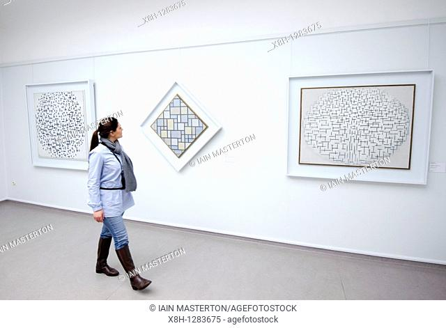 Woman looking at paintings by Piet Mondriaan at Kroller-Muller Museum in The Netherlands