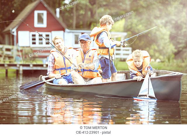 Brothers, father and grandfather fishing from canoe on lake