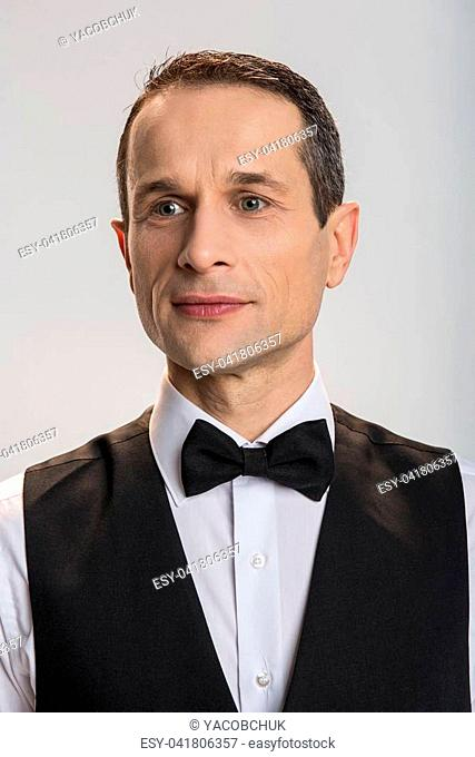 fee04915b699 Serious pensive good looking man gazing aside while musing and standing on  the