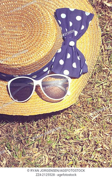 Pretty vintage straw hat with polkdot bow lying on dry Australian grass background. Travel outback australia