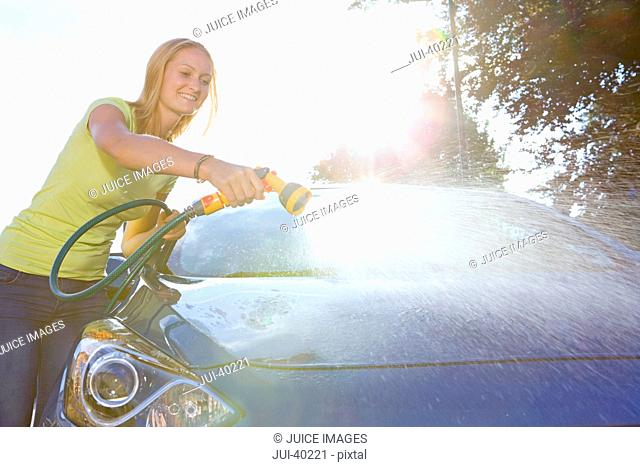 Woman Cleaning Car With Hose At Home