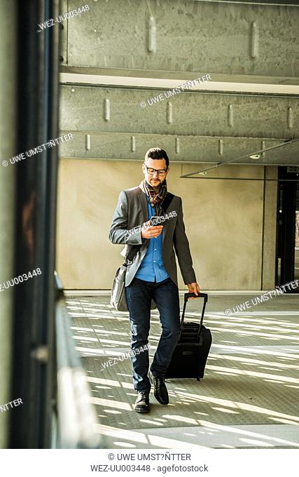 Young businessman walking in car park looking on cell phone