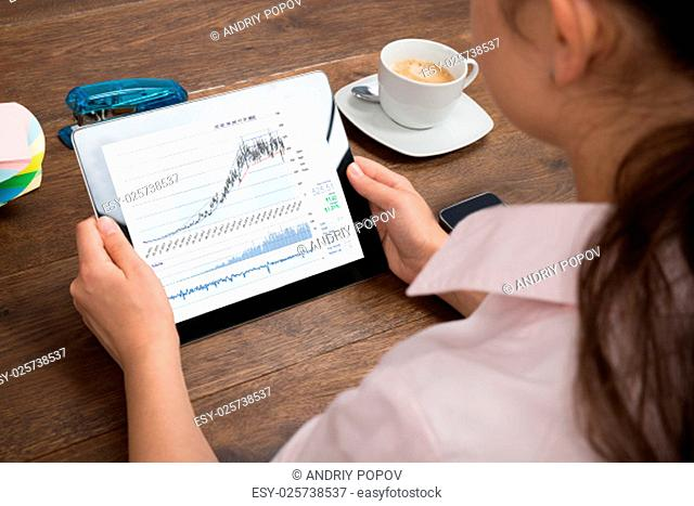 Close-up Of Businesswoman Analyzing Graph On Digital Tablet At Desk