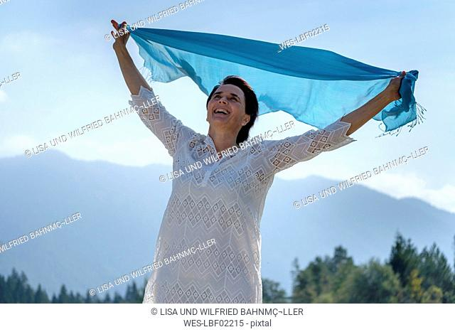 Happy woman holding swaying blue scarf at the riverside, Upper Bavaria, Germany