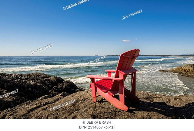 A red muskoka chair on the shore along the coast, Pacific Rim National park, Vancouver Island; British Columbia, Canada