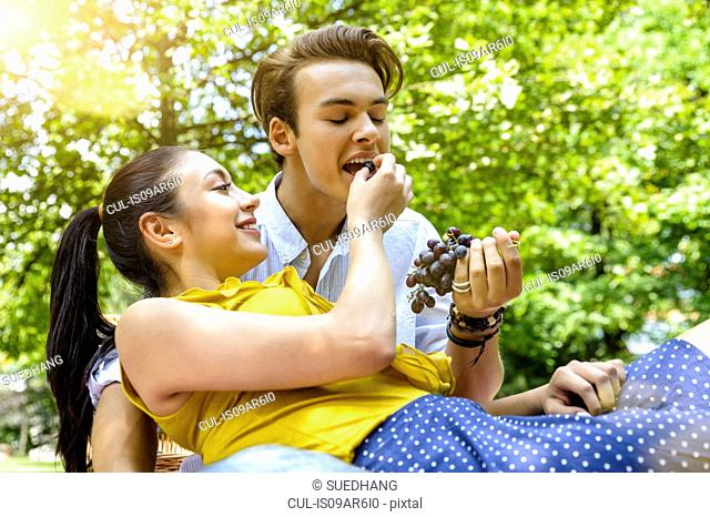 Young woman feeding young man grapes