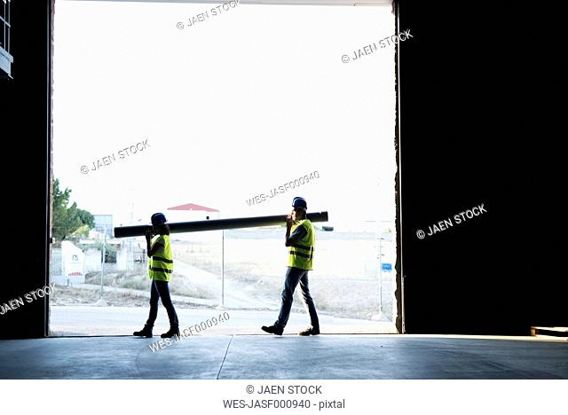 Construction workers carrying pipe in warehouse