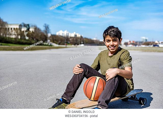 Portrait of smiling boy with longboard and basketball outdoors