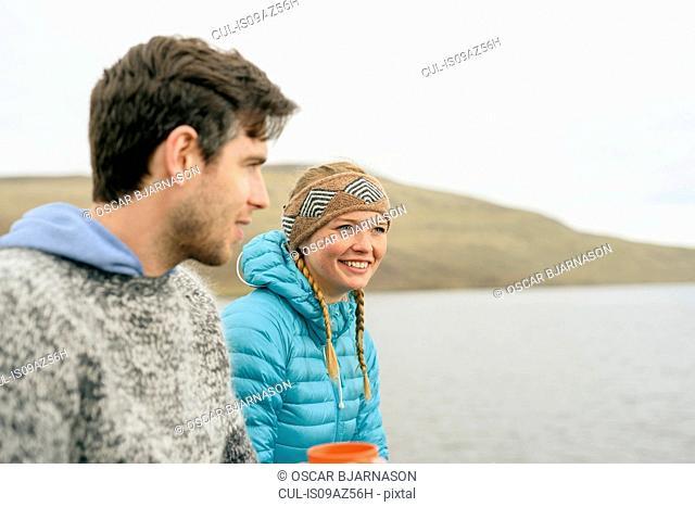 Couple enjoying view on hill, Vagar, Faroe Islands