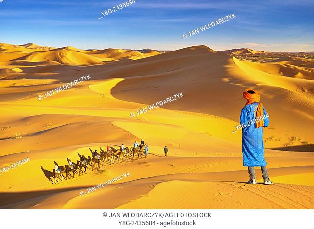 Berber man looking at tourists ride on camels, Erg Chebbi desert near Merzouga, Sahara, Morocco
