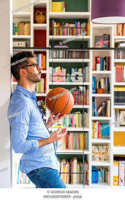 Pensive young man with basketball standing in front of bookshelves at home