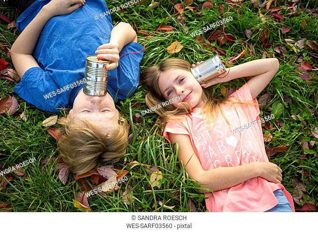 Boy and girl on a meadow having fun with tin can phone