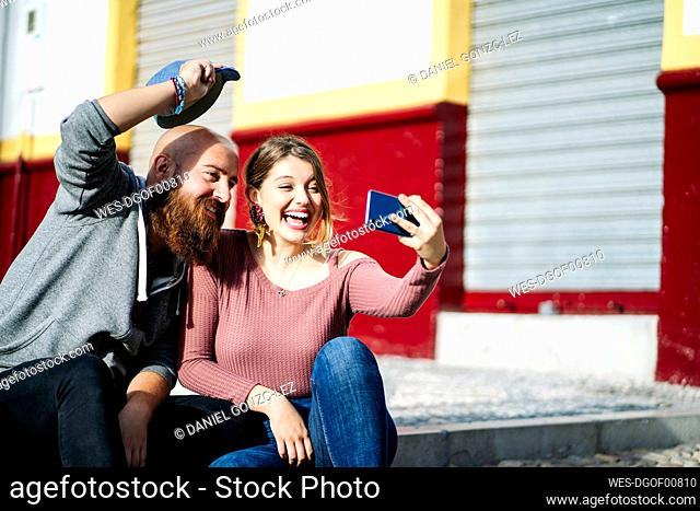 Happy couple taking a selfie in the city