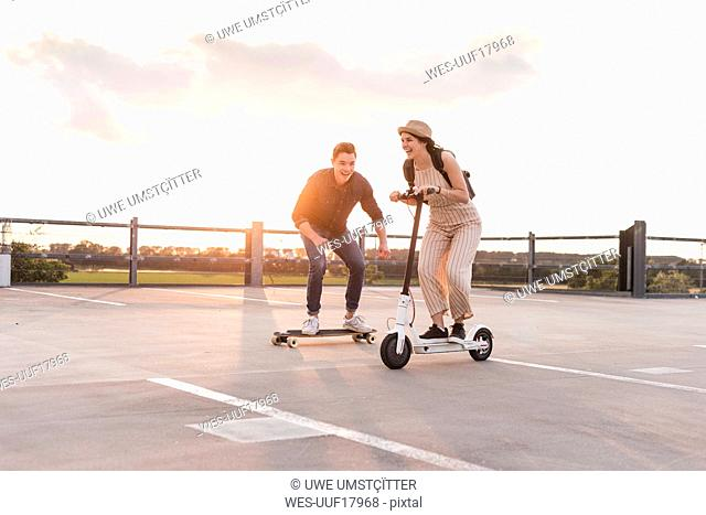 Young man and woman riding on longboard and electric scooter on parking deck at sunset