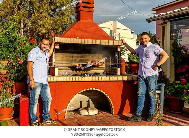 Men Cooking Meat On A Spit At A Restaurant In Sidari, Corfu, Greece
