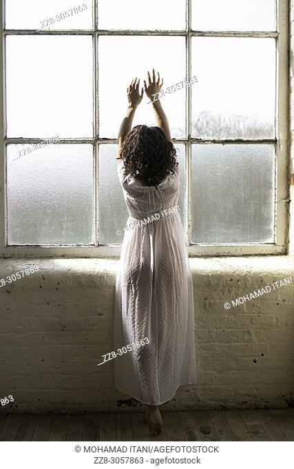 Rear view of a woman standing by the window hands touching the glass