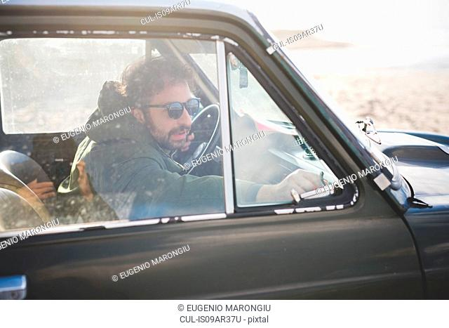 Man in parked vintage car lat beach fastening window