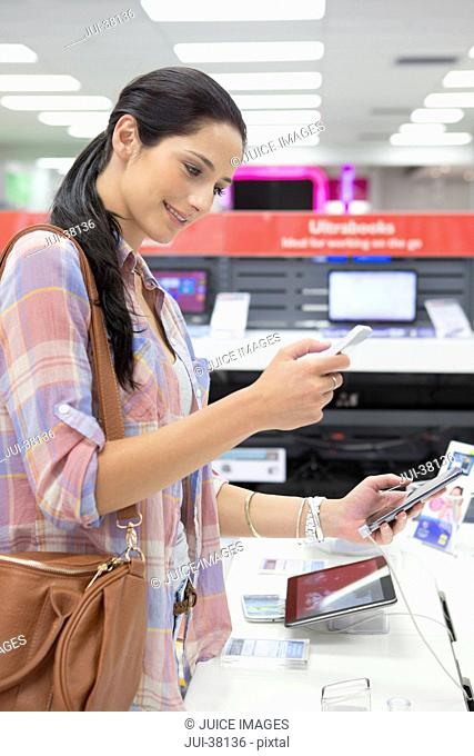 Smiling woman looking at cell phones in electronics store