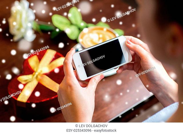 holidays, valentines day, technology and people concept - hands with smartphone, gift box and coffee cup over snow