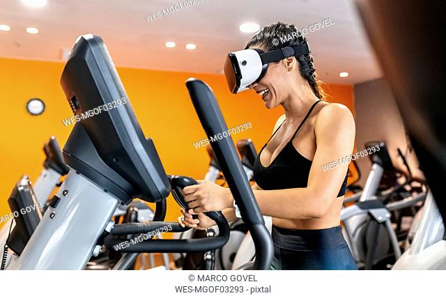 Woman wearing VR glasses on an elliptical traine in the gym