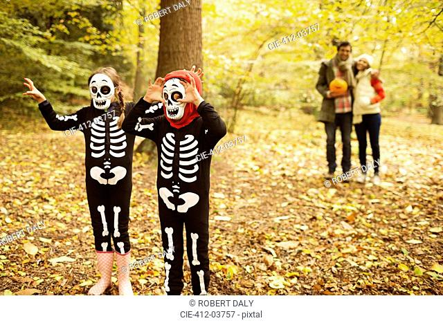 Children in skeleton costumes walking in park