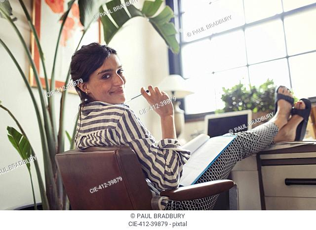 Portrait confident businesswoman working, reviewing paperwork with feet up on desk