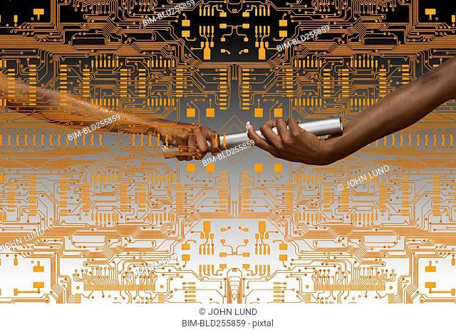 Hands of women passing baton on circuit board
