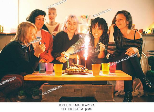 Group of friends celebrating birthday, woman lighting candles on birthday cake