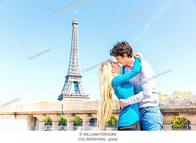Couple in front of eiffel tower kissing, Paris, France