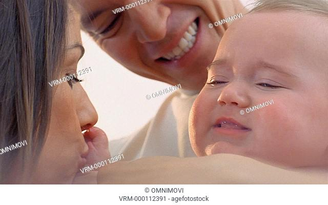 Mother, father and baby hugging and kissing