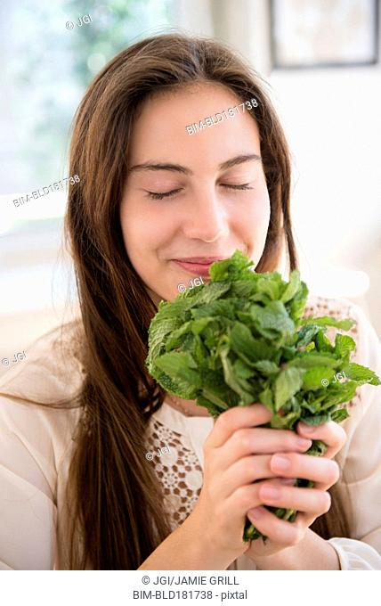 Native American woman smelling herbs