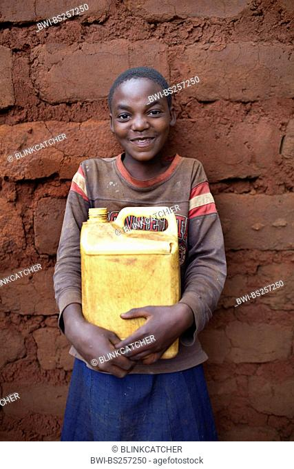 little girl standing at the wall of a recently finished mud brick house with a water canister in hands, Burundi, Karuzi, Buhiga