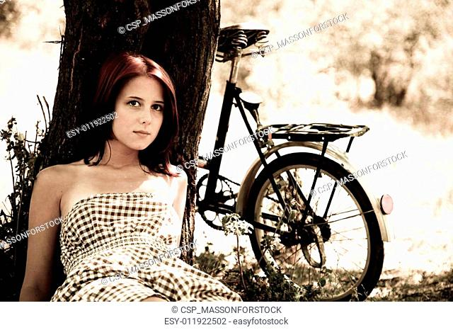 Beautiful girl sitting near bike and tree at rest in forest. Photo in retro style
