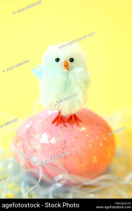 Blue chick standing on Easter egg