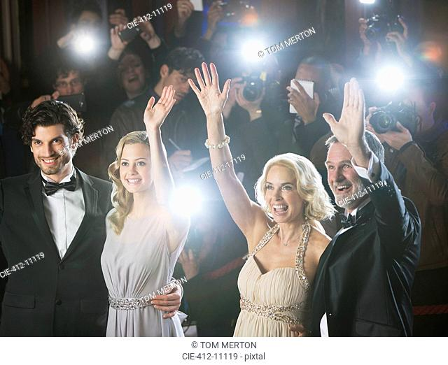 Well dressed celebrity couples waving to paparazzi at red carpet event