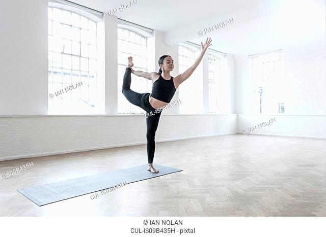Woman in dance studio leg raised, stretching
