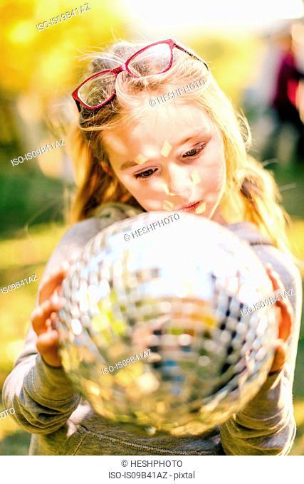 Girl in sunlit garden gazing at disco ball