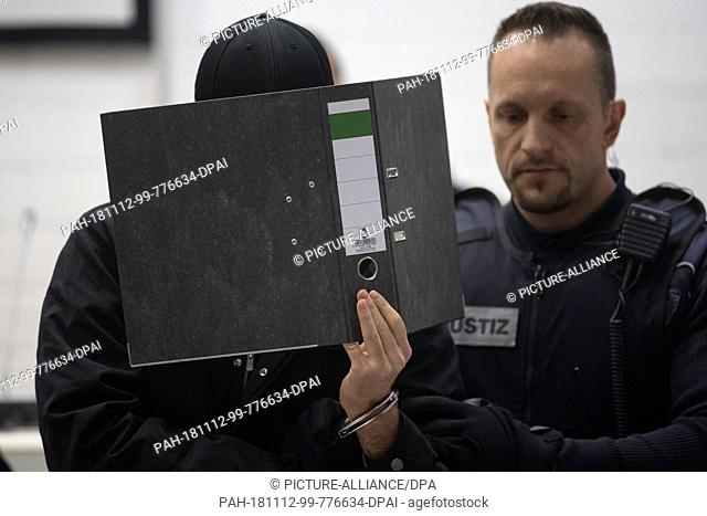 12 November 2018, Baden-Wuerttemberg, Stuttgart: A suspected Islamist (l) holds a folder in front of his face in the courtroom of the Higher Regional Court and...