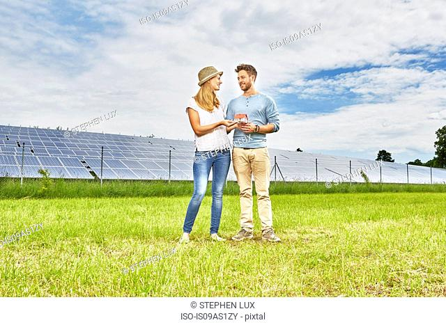 Young couple standing in field, holding small model of house, next to solar farm
