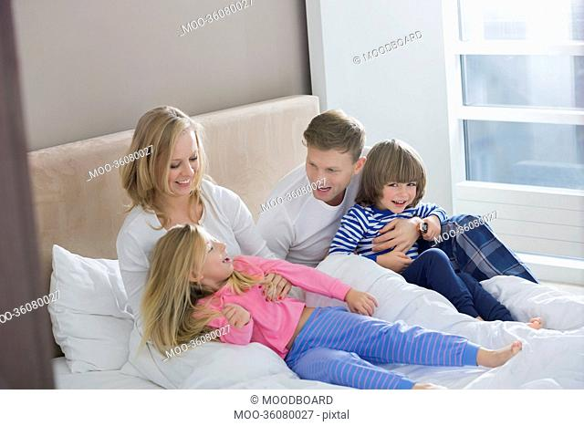 Parents playing with children in bedroom