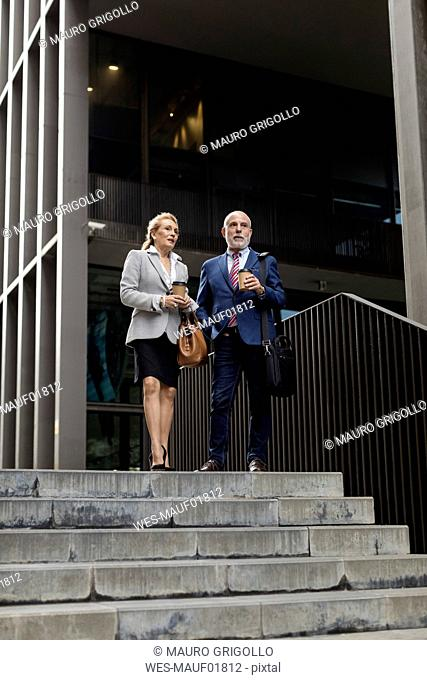 Senior businessman and businesswoman talking outside office building in the city